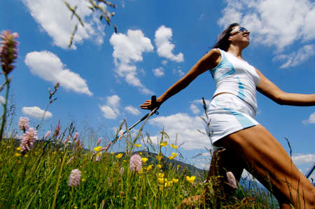 nordic walking: Young woman Nordic walking in meadow Germany low angle view