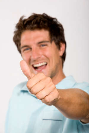 Young man showing thumbs up focus on thumb portrait