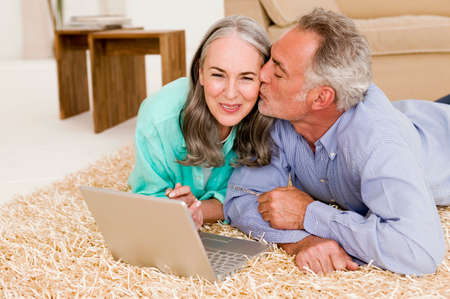 Mature couple lying on carpet with laptop man kissing woman