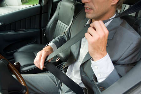 Young man sitting in car using seat belt LANG_EVOIMAGES
