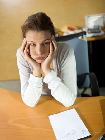 overstress: Tired woman sitting at desk head in hands closeup