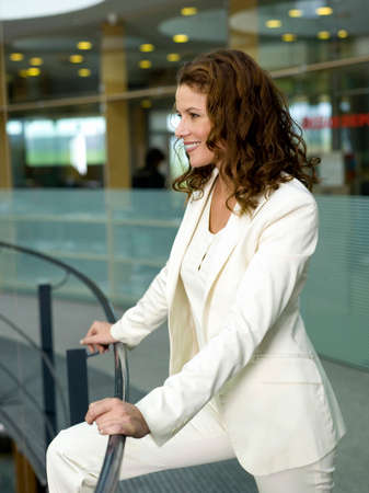 pantsuit: Businesswoman leaning on handrail