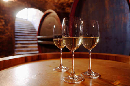 alcohol series: White wine in glasses on wine cask closeup