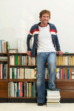Young man standing in front of bookshelf feet on books portrait