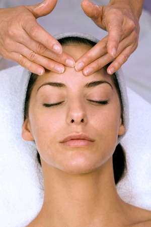 acupressure hands: Young woman receiving forehead massage eyes closed elevated view