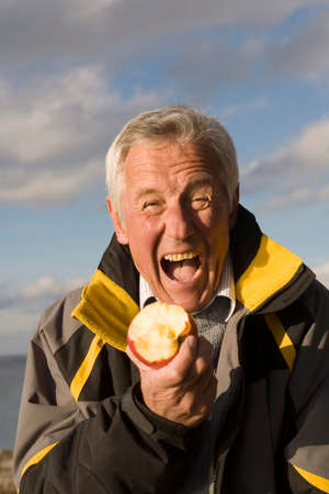 senior adult man: Senior adult man eating apple