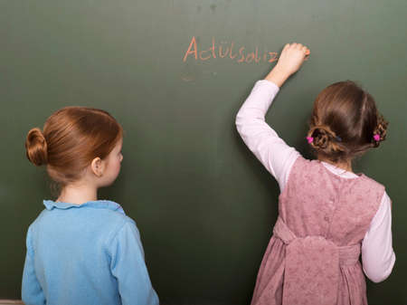 orthography: Girls standing in front of blackboard writing rear view LANG_EVOIMAGES