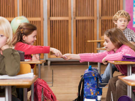 Girls 47 exchanging notes in classroom LANG_EVOIMAGES