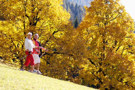 nordic walking: Senior couple Nordic walking side view portrait
