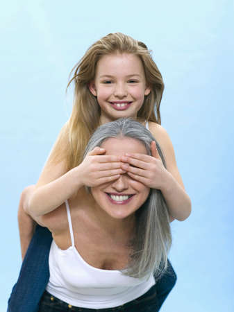 only senior adults: Girl sitting on womans back hiding her eyes LANG_EVOIMAGES