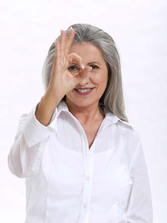 only senior adults: Senior woman making hand gesture LANG_EVOIMAGES