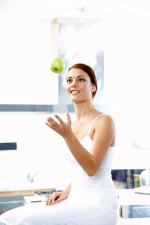Youong woman throwing apple