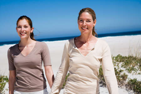 girls at the beach series: Mother and daughter walking on beach hand in hand LANG_EVOIMAGES