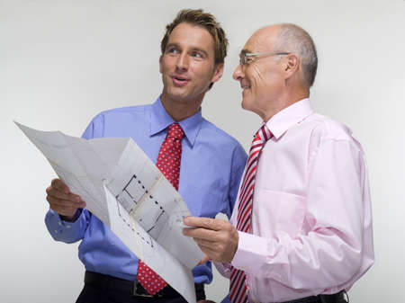 Two businessmen holding construction plan LANG_EVOIMAGES