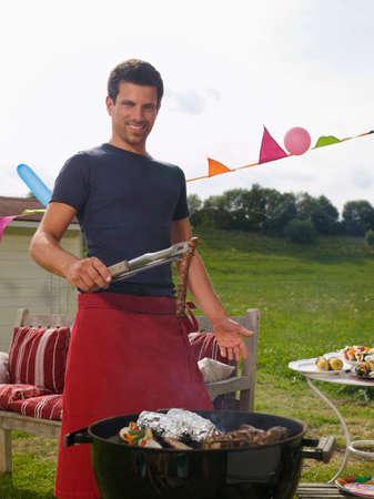 grill tongs sausage: Man preparing barbecue