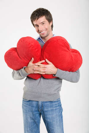 zest for life: Young man holding heartshaped cushions portrait LANG_EVOIMAGES