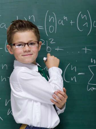 prodigy: Boy 1011 in front of blackboard smiling portrait