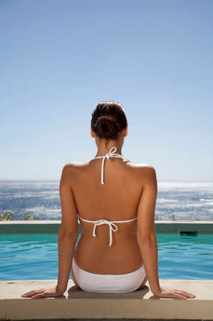 adulthood: Woman sitting at swimmingpool rear view LANG_EVOIMAGES
