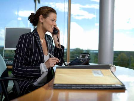 pinstripes: Businesswoman working in office using landline phone