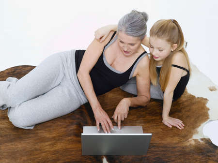 only senior adults: Grandmother and granddaughter using laptop portrait LANG_EVOIMAGES