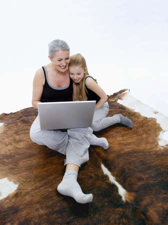 cow hide: Grandmother and granddaughter using laptop portrait LANG_EVOIMAGES