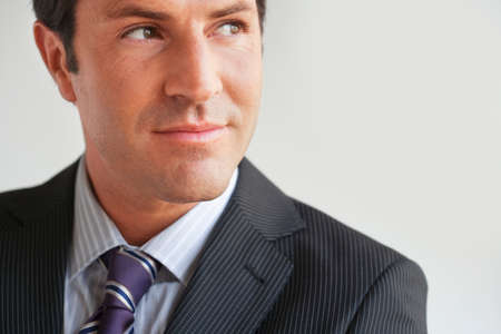 only one mid adult male: Portrait of business man looking sideways close up