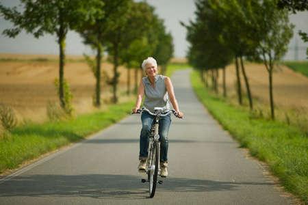 only senior adults: Senior woman biking on road LANG_EVOIMAGES