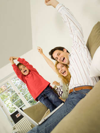 Young family in living room cheering