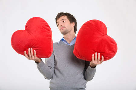 only mid adult men: Young man holding heartshaped cushions portrait LANG_EVOIMAGES
