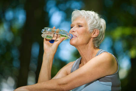 only senior adults: Senior woman drinking from water bottle portrait LANG_EVOIMAGES
