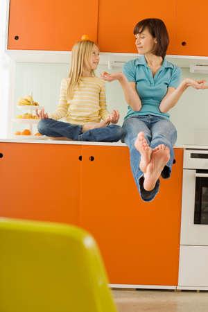 frutas divertidas: Madre e hija 89 en la hija de cocina equilibrio de color naranja en la cabeza LANG_EVOIMAGES