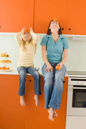 Mother and daughter 89 in the kitchen balancing orange on head looking up