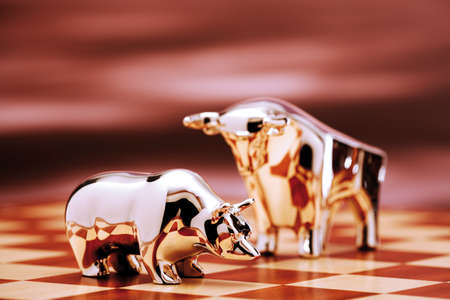 tablero de ajedrez: Bull y oso estatuilla en el primer del tablero de ajedrez