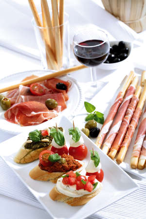 grissini: Grissini with parma ham and olives and mozzarella with tomatoes italian starters LANG_EVOIMAGES