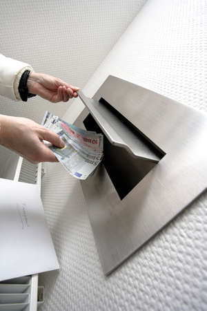 wasting away: Human hand throwing Euro notes in letterbox closeup