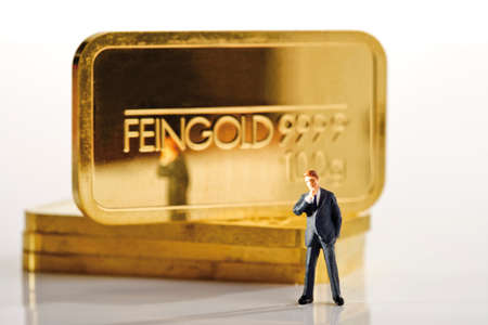 solicitude: Businessman figurine in background gold bars