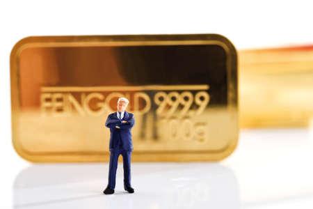 male likeness: Businessman figurine in background gold bars