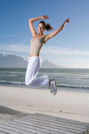 exaltation: South Africa Cape Town Young woman jumping on beach LANG_EVOIMAGES
