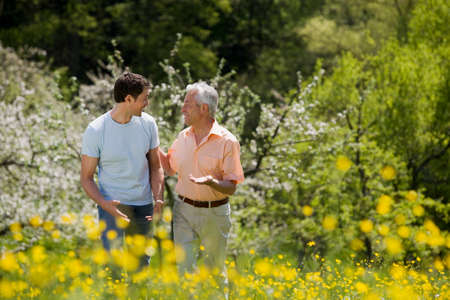Germany Baden Wrttemberg Tbingen Mature father and adult son walking through meadow