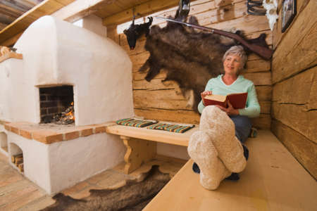 only senior adults: Senior woman in hunting lodge holding a book