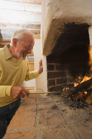 stoking: Senior man stoking fire in fireplace LANG_EVOIMAGES