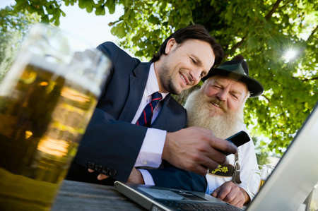beer garden: Germany Bavaria Upper Bavaria Senior Bavarian man and young businessman with laptop in beer garden