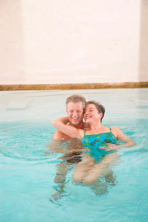 zest for life: Mature couple in swimmingpool smiling portrait LANG_EVOIMAGES