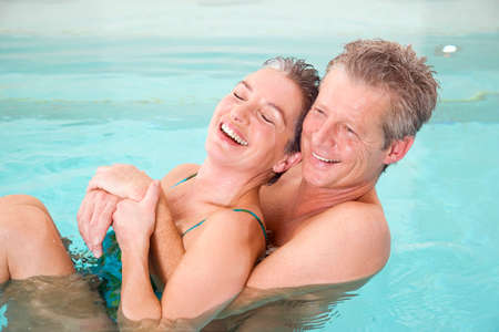 swimmingpool: Mature couple in swimmingpool portrait LANG_EVOIMAGES
