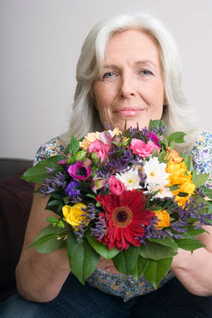only senior adults: Senior woman holding bunch of flowers portrait