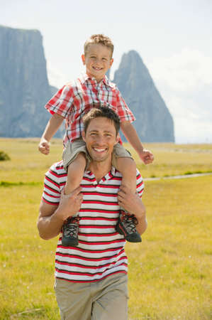 shoulder carrying: Italy Seiseralm Fahter carrying son 67 on his shoulder smiling portrait