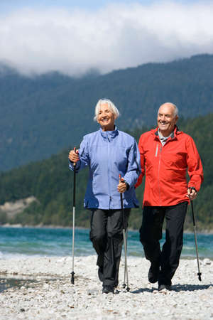 Germany Bavaria Walchensee Senior couple Nordic Walking on lakeshore