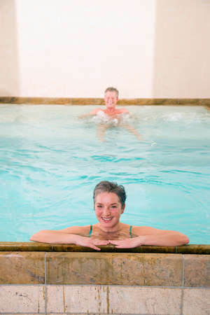 Mature couple in swimmingpool smiling portrait LANG_EVOIMAGES