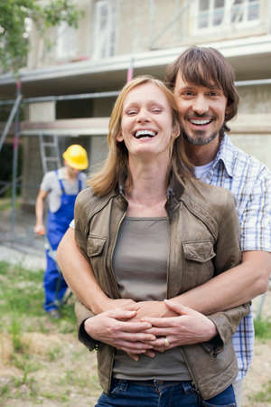 Young couple at site embracing construction worker in background