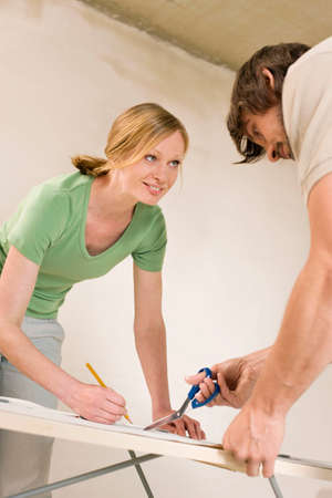 Young couple renovating cutting wallpaper